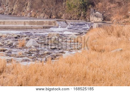 Landscape of a rock filled river with a man made waterfall used to aerate the water
