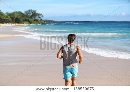 Man athlete running away from behind on beach at sunset. Male runner doing cardio exercise workout on sand with ocean background. Healthy active life on travel destination.