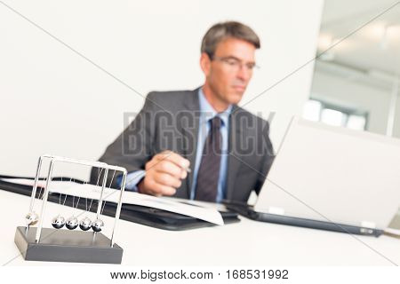 manager sitting at his desk, working on his laptop