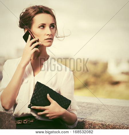 Young business woman with handbag calling on mobile phone  Stylish fashion model outdoor