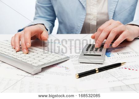 Financial accounting  Business woman using calculator and computer keyboard