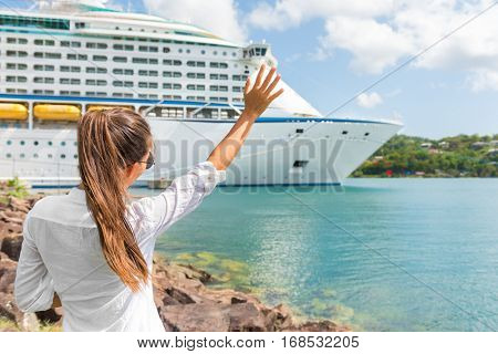Happy joyful woman waving hello or goodbye hand sign to cruise ship. Caribbean luxury travel vacation concept. Boat leaving harbor, tourist people greeting.