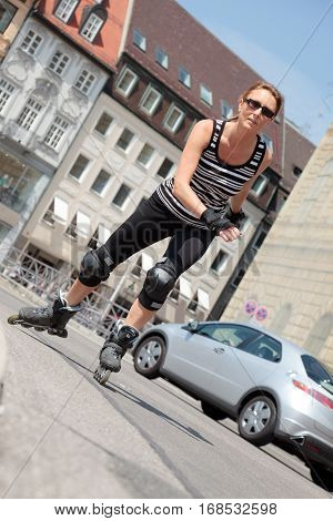 a woman in her 40s is rollerskating in the city