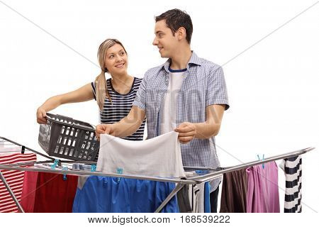 Man picking up clothes from a clothing rack dryer with a woman holding an empty laundry basket isolated on white background
