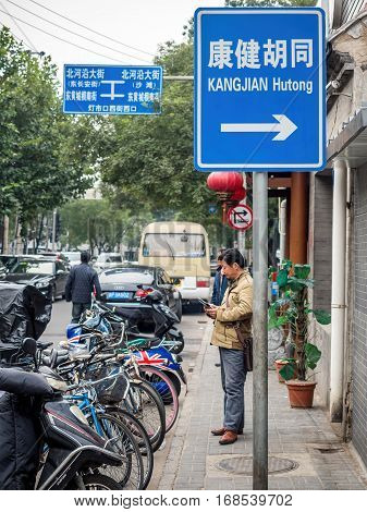 Beijing, China - Oct 30, 2016: Along Dengshikou West Street. A sign showing direction to Kangjian Hutong. Hutongs are narrow traditional streets or alleys commonly found in Old Beijing.