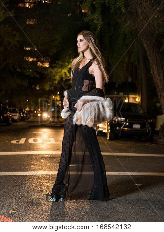 Beautiful young girl wearing black evening dress and fur jacket walking on the city street at night time