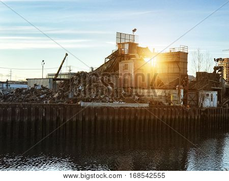 Car scrap metal dump recycling industrial factory at sunset time
