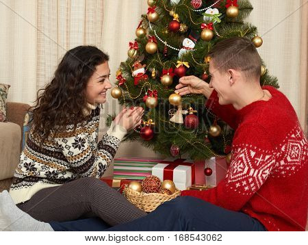 Young couple decorate christmas fir tree. Home interior with gifts. New year holiday concept. Love and tenderness.
