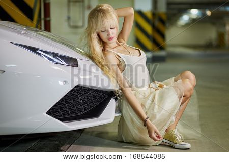 Young blonde woman sits leaning back to front bumper of modern white car at underground parking.