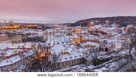 Prague in winter time, view on snowy roofs with historical buildings.