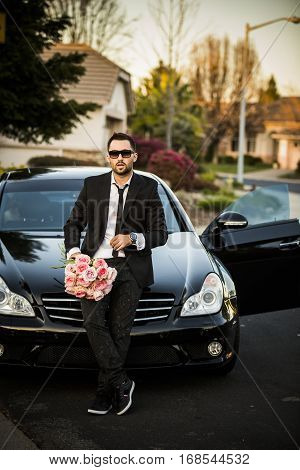 handsome boyfriend in black suit waiting his girlfriend on street. With flowers.