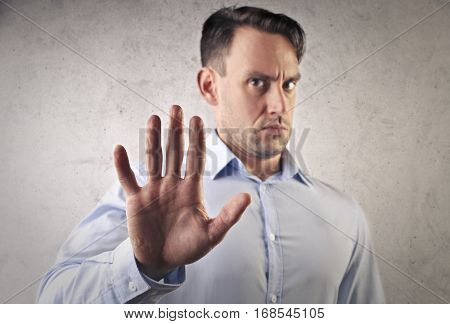Man in blue shirt saying STOP with his hand