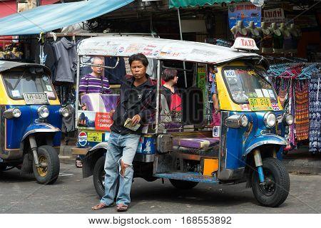 BANGKOK, THAILAND - JANUARY 06, 2017: The driver of a tuk-tuk waiting for passengers