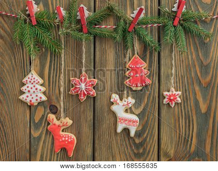 Christmas gingerbread cookies hanging on rope on wooden background.
