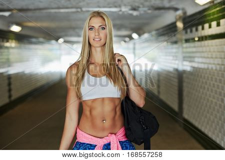 Attractive fit woman in sport clothing walking in a tunnel on the way to fitness training.