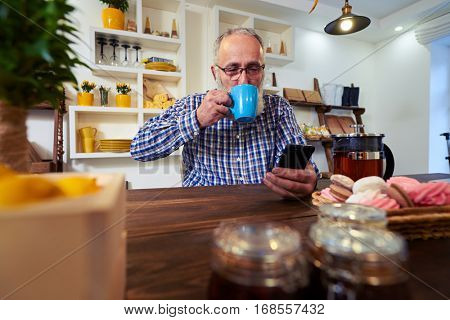 Close-up of delighted smiling mature man enjoying a cup of tea while holding a telephone in a hand. Taking a sip of tea. Kitchen interior. Teapot and sweets standing on the table