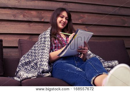 Mid shot of a girl writing in a notebook while sitting on the sofa at home. Isolated over wooden background