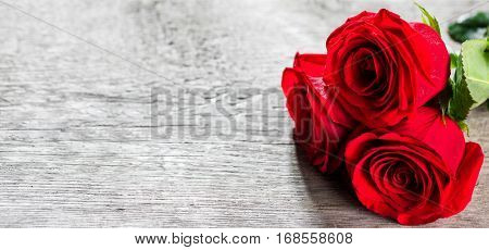 Three beautiful red roses on aged wooden background