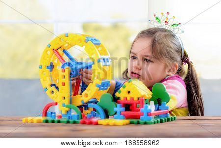 Ambitious Little Girl Is Playing With Toys At Home
