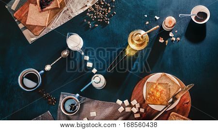 Breakfast still life with toast, honey, coffee, milk, jam and sugar composed in a form of a constellation Big Dipper