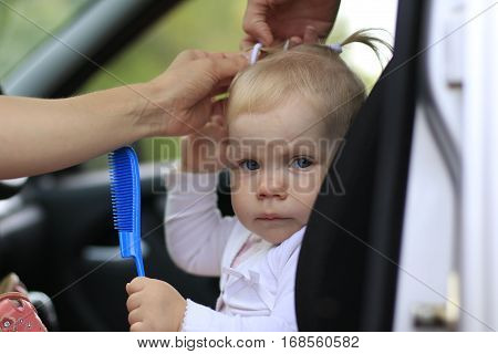 Sad Baby In The Car And The Woman's Hands Are Making The Hair Style