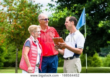 Golf pro with senior woman and man analyzing results