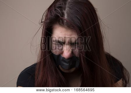 Brunette hostage with gray tape
