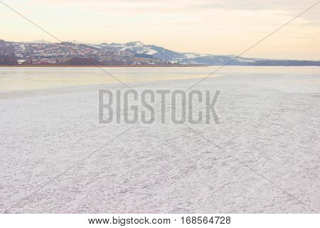 mountain covered with snow and frozen river