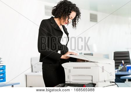 Businesswoman standing at the copying machine