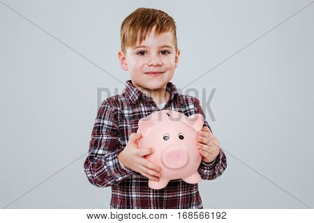 Smiling Young boy with moneybox in hands looking at camera. Isolated gray background