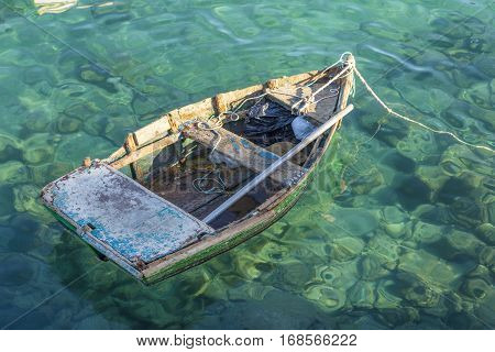 old rotten fisher boat swims at the ocean