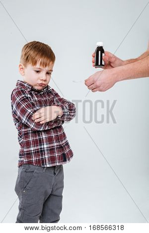 Sad little boy standing and refusing to take a medicine over white background