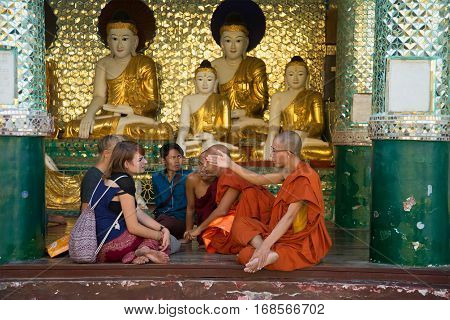 YANGON, THAILAND - DECEMBER 17, 2016: Buddhist monks communicate with the European tourists in one of the temples of the Shwedagon pagoda