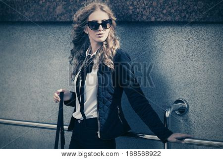 Young blond woman in sunglasses at the wall  Stylish fashion model outdoor