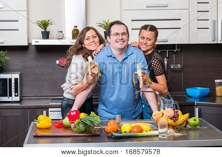 Two young women are fed bananas midle age man in the kitchen