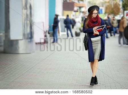 Young beautiful businesswoman walking on crowded street