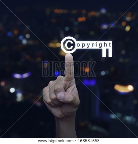 Hand pressing copyright key icon over blur colorful night light city tower Copyright and patents concept