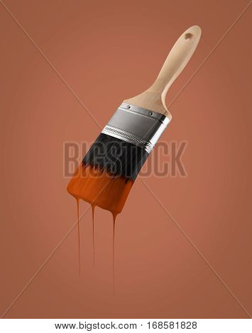 Paintbrush loaded with brown color dripping off the bristles on brown background.