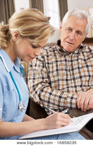 Senior Man Talking To Health Visitor At Home