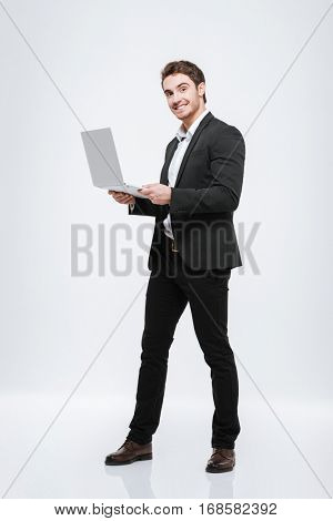 Picture of cheerful young caucasian businessman standing at studio. Isolated over white background. Look at camera and holding laptop computer in hands.