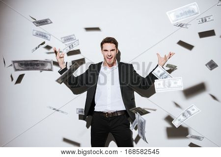 Picture of handsome businessman posing at studio and look at camera while throws away money. Isolated over white background.