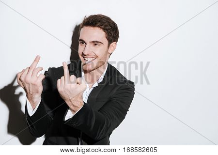 Photo of cheerful businessman posing at studio and look aside while holding cigarette and showing middle finger. Isolated over white background.