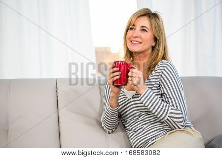 Woman day dreaming holding a cup