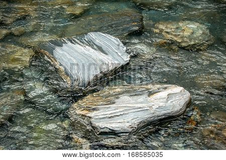 Water polished rocks in the current of Thunder Creek on the South Island of New Zealand