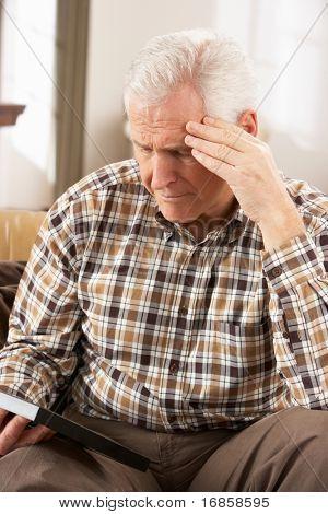 Sad Senior Man Looking At Photograph In Frame
