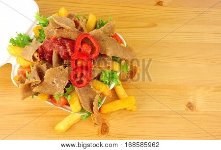 Doner kebab meat and chips with salad and chilli sauce in a take away tray on a wood background