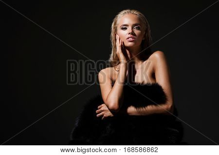 hairstyle, haircare and fashion concept - natural blond woman portrait with beautiful hair in fur coat on dark background