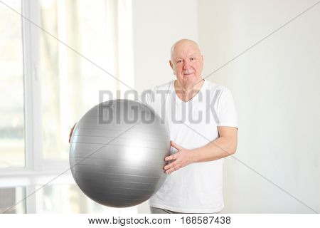 Senior man with fitball in rehabilitation center