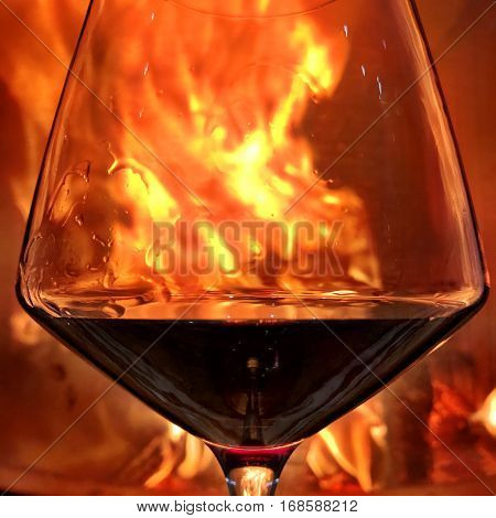 Glass of Wine close up in front of a fireplace with hot burning fire.