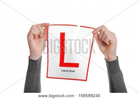 Hands of young man tearing learner driver sign on white background